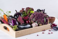 Assortment of fresh raw purple homegrown vegetables on dark wooden table. Cauliflower  eggplant  beets  carrots  potatoes  plums  basil  onions  garlic  beans Stock Photography