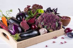 Assortment of fresh raw purple homegrown vegetables on dark wooden table. Cauliflower  eggplant  beets  carrots  potatoes  plums  basil  onions  garlic  beans Stock Photos