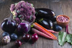Assortment of fresh raw purple homegrown vegetables on dark wooden table. Cauliflower eggplant beets carrots potatoes plums basil onions garlic beans lettuce Stock Photos