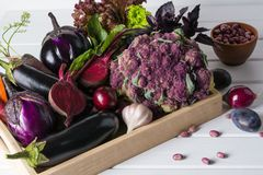 Assortment of fresh raw purple homegrown vegetables on dark wooden table. Cauliflower eggplant beets carrots potatoes plums basil onions garlic beans lettuce Stock Photo