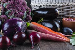 Assortment of fresh raw purple homegrown vegetables on dark wooden table. Cauliflower eggplant beets carrots potatoes plums basil onions garlic beans lettuce Stock Images