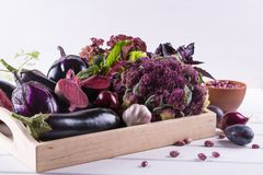 Assortment of fresh raw purple homegrown vegetables on white table. Cauliflower, eggplant beets  carrots  potatoes plums  basil  onions garlic  beans lettuce Royalty Free Stock Image