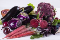 Assortment of fresh raw purple homegrown vegetables on white table. Cauliflower eggplant  beets  carrots  potatoes  plums  basil  onions garlic  beans  lettuce Royalty Free Stock Photography