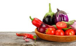 Assortment of fresh raw vegetables on old wooden table with white background. Tomato, eggplant, onion, chili pepper. Stock Image