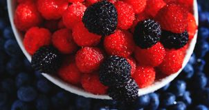 Assortment of fresh red and black berries. Top view of raspberries in the plate on background of blueberries. Ripe and juicy fresh. Raspberries close-up royalty free stock photography