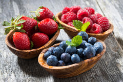 Assortment of fresh seasonal berries in a wooden bowl Stock Photo