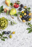 Assortment of fresh summer fruit - grapes, pears, apples, plums on a light background, top view. Stock Photography