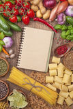 Fresh vegetables and blank recipe book. Assortment of fresh vegetables and blank recipe book on a wooden background royalty free stock photo