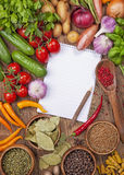 Assortment of fresh vegetables. And blank recipe book on a wooden background royalty free stock photo