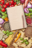Assortment of fresh vegetables and blank recipe book. On a wooden background stock images