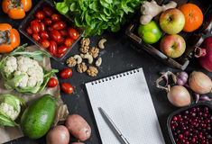 Assortment of fresh vegetables and fruit, clean Notepad on a dark background. Concept of a healthy diet and planning. Stock Image