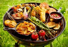 Assortment of fresh vegetables grilling on a BBQ. Large assortment of fresh vegetables grilling on a Portable BBQ outdoors on green grass in summer over the hot royalty free stock photo