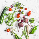 Assortment of fresh vegetables on a light background - zucchini, peppers, beets, tomatoes, green beans, onion. Stock Photos