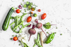 Assortment of fresh vegetables on a light background - zucchini, peppers, beets, tomatoes, green beans, onion. Food background. Free space for text, top view Stock Photo