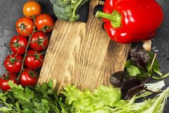 Assortment of fresh vegetables pepper, cherry tomatoes, onions,. Garlic, spinach, broccoli on a dark background. Wooden cutting board. Top view, copy space Stock Image