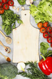 Assortment of fresh vegetables pepper, cherry tomatoes, onions. Garlic, spinach, broccoli and spices on a light background. Wooden cutting board. Top view Royalty Free Stock Photo