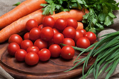 Assortment of fresh vegetables. Tomatoes, carrots, parsley on wooden board Stock Photo