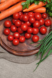 Assortment of fresh vegetables. Tomatoes, carrots, parsley on wooden board Stock Images