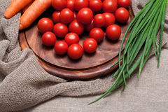 Assortment of fresh vegetables. Tomatoes, carrots, parsley on wooden board Stock Image
