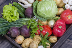 Assortment of fresh vegetables on wooden tray background. Assortment of fresh raw vegetables arranged on a rustic wooden table tray. Selection includes carrot Royalty Free Stock Photo