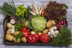 Assortment of fresh vegetables on wooden tray background. Assortment of fresh raw vegetables arranged on a rustic wooden table tray. Selection includes carrot Royalty Free Stock Image