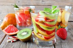 Assortment of fruit infused water against rustic wood Royalty Free Stock Photos