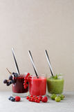 Assortment of fruit  smoothies in glass with straws on white bac. Assortment of fruit  smoothies in glass with straws on white stone background Royalty Free Stock Photo