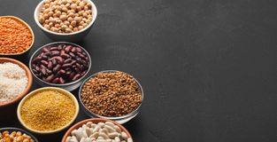 Various gluten free groats on black background with copy space. Assortment of gluten free grains in bowls on black background, copy space Royalty Free Stock Photos