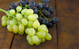 Assortment of grapes on a  wooden table Stock Image