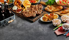 Assortment of grilled barbecue food. Vegetables, salad, ice cream dessert and bottles of beer on a slate background with copy space Stock Images