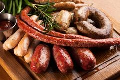 Assortment of grilled sausages. Assortment of grilled sausages on a wooden board Royalty Free Stock Photography