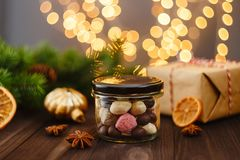 Assortment of handmade candies in glass jar with Christmas decor. Assortment of colorful handmade candies in glass jar on wooden background with Christmas Royalty Free Stock Images
