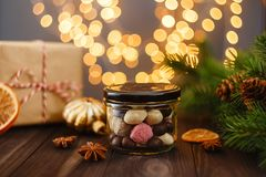 Assortment of handmade candies in glass jar with Christmas decor. Assortment of colorful handmade candies in glass jar on wooden background with Christmas Royalty Free Stock Photography