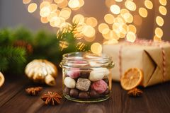 Assortment of handmade candies in glass jar with Christmas decor. Assortment of colorful handmade candies in glass jar on wooden background with Christmas Royalty Free Stock Photo