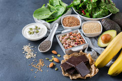 Assortment of healthy high magnesium sources food. Healthy food nutrition dieting concept. Assortment of high magnesium sources. Banana chocolate spinach chard Stock Photos