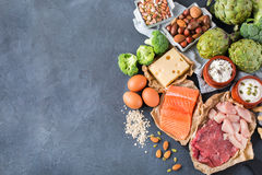 Assortment of healthy protein source and body building food. Meat beef salmon chicken breast eggs dairy products cheese yogurt beans artichokes broccoli nuts Royalty Free Stock Photography