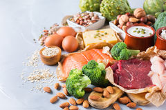 Assortment of healthy protein source and body building food. Meat beef salmon chicken breast eggs dairy products cheese yogurt beans artichokes broccoli nuts Stock Images