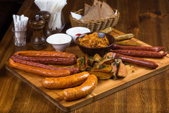 Assortment hot sausages serving on wooden board Royalty Free Stock Image