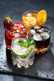 Assortment of iced fruit drinks on a dark background, vertical. Top view, closeup stock photo