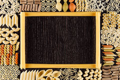 Assortment italian dry pasta on dark brown wooden board with blank copy space as decorative frame background. Royalty Free Stock Photo