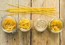 Assortment of Italian dry pasta in the glass jars on the wooden background Stock Image