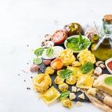 Italian food and ingredients, ravioli pasta tortellini pesto tomato sauce. Assortment of italian food and ingredients, ravioli with ricotta and spinach pasta Stock Images