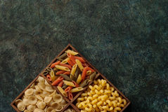 Assortment Italian pasta. Various types and shapes of Italian pasta on dark background, top view Stock Photos