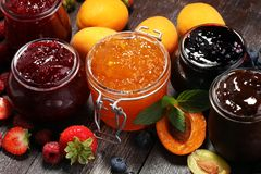 Assortment of jams, seasonal berries, apricot, mint and fruits. Marmalade or confiture stock image
