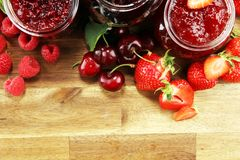 Assortment of jams, seasonal berries, cherry, mint and fruits in glass jar royalty free stock photography