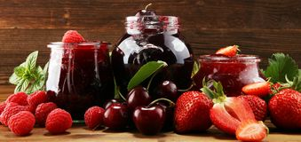Assortment of jams, seasonal berries, cherry, mint and fruits in glass jar stock image