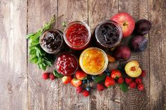 Assortment of jams, seasonal berries, plums, mint and fruits. Assortment of jams, seasonal berries, plums, mint and fruits royalty free stock images