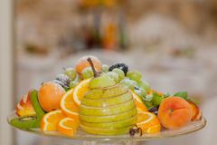 Assortment of juicy fruits on wooden table, on bright background.  royalty free stock photography