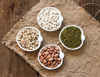 Assortment of legumes in bowls on wooden table Royalty Free Stock Images