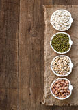 Assortment of legumes in bowls on wooden table Stock Photos